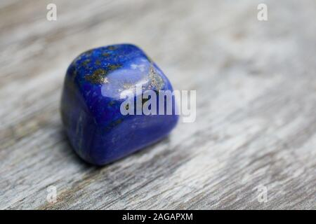 close up of blue gemstone lapis lazuli on wooden background with copy space - Stock Photo