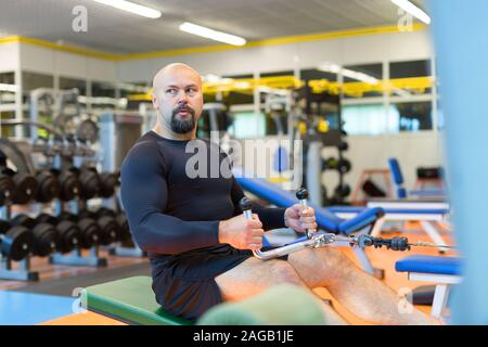 Middle aged athlete doing workouts on a back with power exercise machine in a gym club. Healthy lifestyle and motivation concept. - Stock Photo