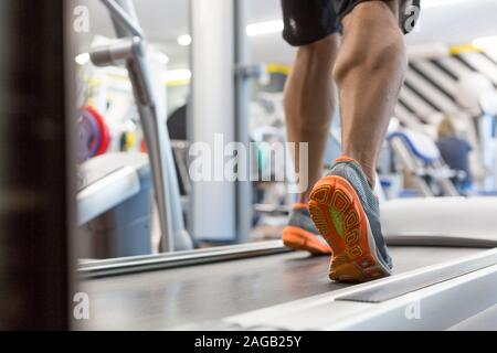 Close up male muscular feet in sneakers running on the treadmill at gym. Fitness, workout and healthy lifestyle concept.