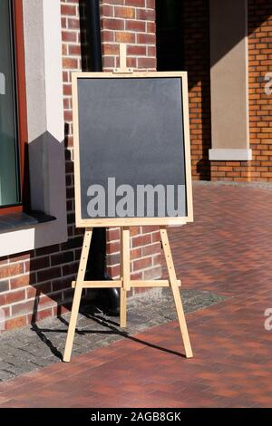 Chalkboard menu standing on the street, sign. Empty space concept for advertising, mockup. - Stock Photo