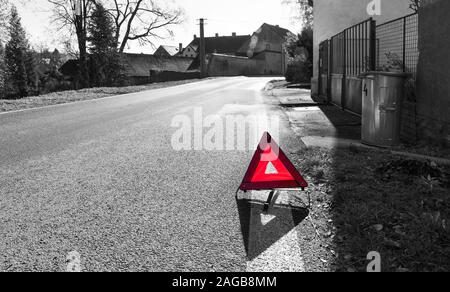 Attention! Danger on the way. Red warning triangle. Road sign on black and white village background. Caution symbol on asphalt surface. Traffic rules. - Stock Photo