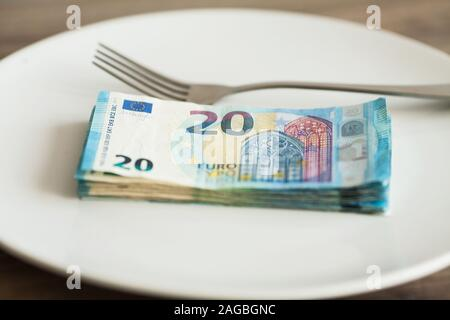 Money lying on the plate with fork. Euros photo. Greedy corruption concept. Bribe idea - Stock Photo