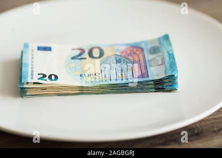 Money lying on the plate. Euros photo. Greedy corruption concept. Bribe idea.