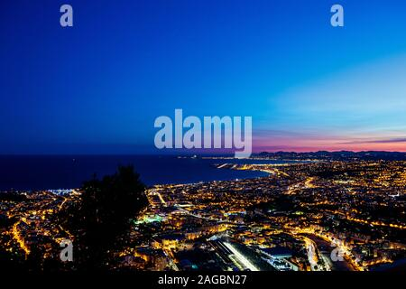 A high angle shot of a beautifully illuminated cityscape and a sea in Nice, France - Stock Photo