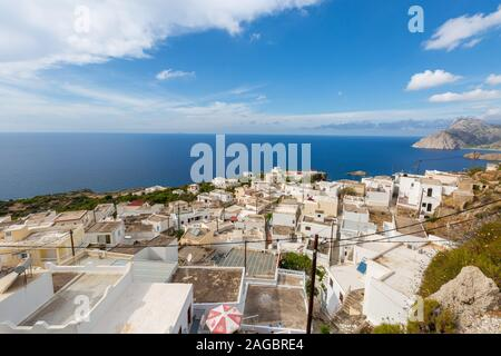 A high angle view of white buildings surrounded by mountains and sea under a blue sky in Karpathos - Stock Photo