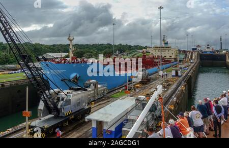 Panama-11/6/19: A view of the ship Maersk Corsica going throught the Panama Canal while cruise ship passengers look on from the oppsite side of the ca - Stock Photo
