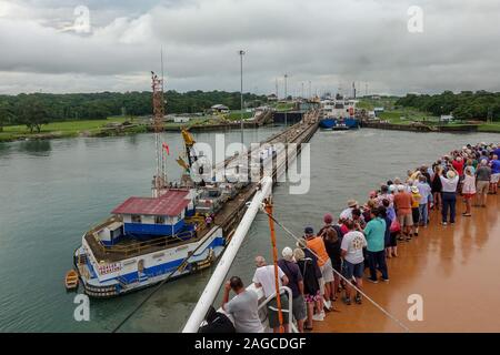 Panama-11/6/19: A view of a ship  going throught the Panama Canal while cruise ship passengers look on. - Stock Photo