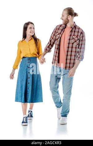full length view of happy young couple in casual outfit walking and holding hands isolated on white - Stock Photo