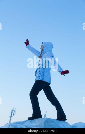 Sporty woman stretching outside surrounded by snow and ice in the winter at Koli National Park in Finland - Stock Photo