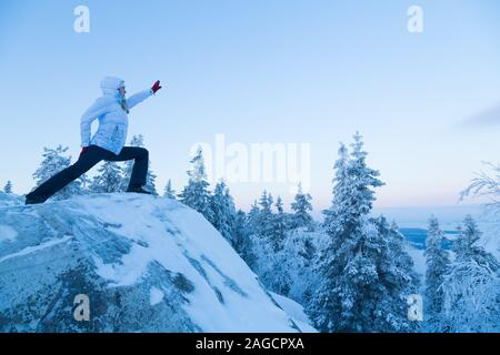 Woman doing yoga poses outside in the winter at Koli National Park Finland - Stock Photo