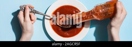 Cropped view of woman pouring ketchup from bottle on plate on blue background, panoramic shot Stock Photo