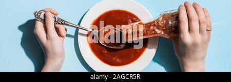 Cropped view of woman pouring ketchup in plate with spoon on blue background, panoramic shot Stock Photo