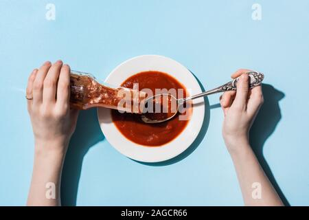 Cropped view of woman pouring ketchup from bottle on plate on blue background Stock Photo