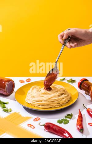 Cropped view of woman pouring ketchup on spaghetti beside chili peppers and cilantro on white surface isolated on yellow Stock Photo