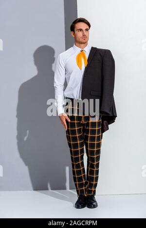 handsome man in plaid trousers standing on white and grey - Stock Photo