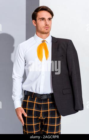 handsome man in plaid trousers on grey and white - Stock Photo
