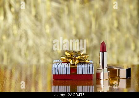 Gift box with golden bows and red lipstick on a gold blurred background. Holiday concept with copy spase. - Stock Photo
