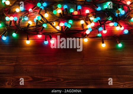Christmas border with colorful garland. Christmas background on dark wooden desk. Flat lay, top view, copy space. - Stock Photo