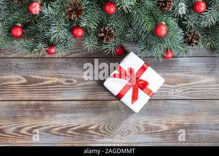 Christmas border with fir branches, red balls, cones and gift on a wooden background. Happy new year. Space for text. Winter concept. Greeting card. - Stock Photo