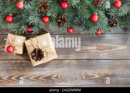 Christmas border with fir branches, red balls, cones and gifts on a wooden background. Happy new year. Space for text. Winter concept. Greeting card. - Stock Photo