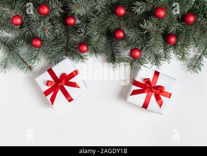 Christmas border with fir branches, red balls and gifts on a white background. Happy new year. Space for text. Winter concept. Greeting card. - Stock Photo
