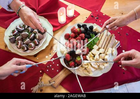 overhead view of hands dipping fruit in chocolate fondue - Stock Photo