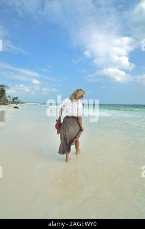 Woman walks the beach in Mexico - Stock Photo
