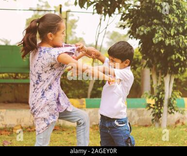 Two little siblings fighting with each other at park - Kids hitting and pulling dress due to conflict at school. - Stock Photo