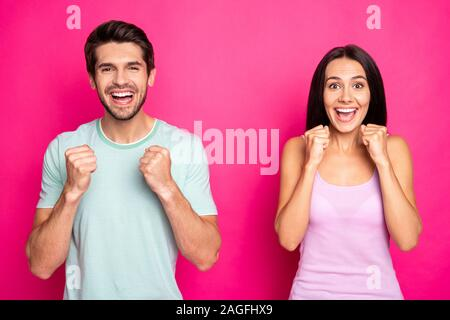 Photo of crazy couple guy and lady raising fists sportive cheerleading for football team wear casual clothes isolated vibrant pink color background - Stock Photo