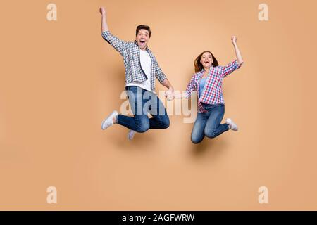 Hooray. Full size photo of two people crazy lady guy jumping high celebrating best win of football team raising fists wear casual checkered jeans - Stock Photo