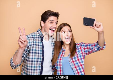 Close-up portrait of his he her she nice attractive lovely funky cheerful cheery couple wearing checked shirt taking selfie showing v-sign isolated - Stock Photo