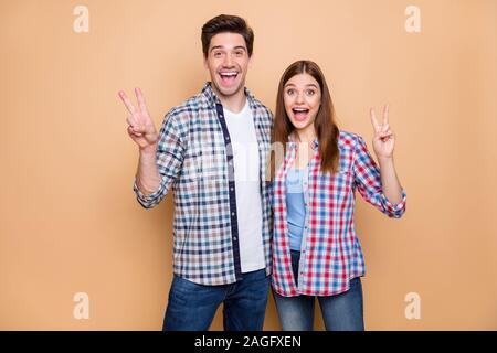 Portrait of his he her she nice attractive lovely charming funky glad cheerful cheery couple wearing checked shirt showing v-sign embracing isolated - Stock Photo
