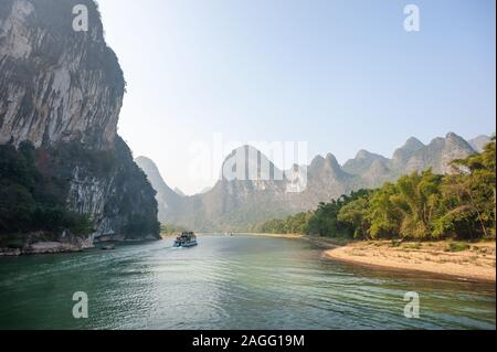 Boat on Li river cruise and karst formation mountain landscape in the fog between Guiling and Yangshuo, Guangxi province, China - Stock Photo