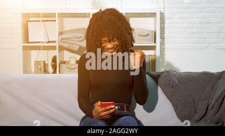 African American girl looks at red smartphone and gets happy showing raised fist at home - Stock Photo