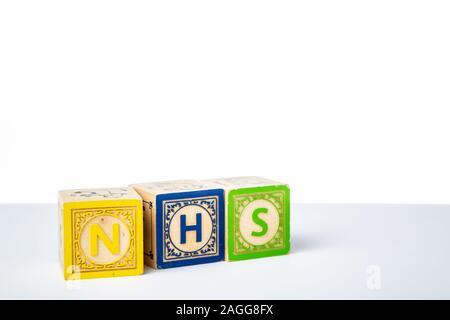 Childrens Wooden Alphabet Blocks Spelling the Word NHS - Stock Photo
