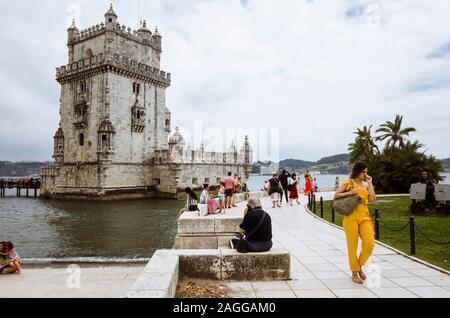 Lisbon, Portugal : Tourists walk past the Unesco listed Belém Tower designed in 1515 by Francisco de Arruda to defend the city's harbour. - Stock Photo