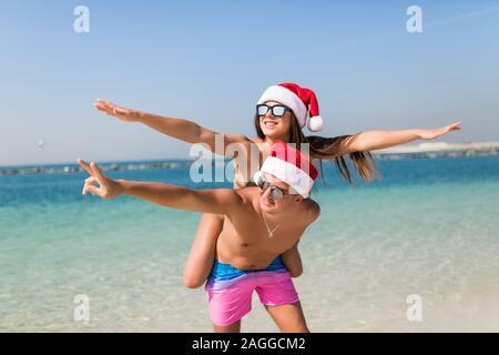 Christmas vacation beach couple doing piggyback fun. Paradise beach travel bikini woman having fun man carrying girl laughing in christmas santa hat. - Stock Photo