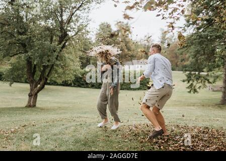 Young man throwing leaves playfully at woman in countryside