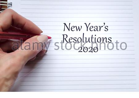 New Year's Resolutions Text on Note Pad - Stock Photo