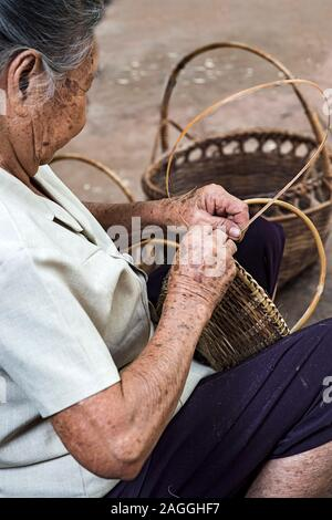 Skillful hands of a local woman weaving a basket, Ban Done Keo, Laos - Stock Photo