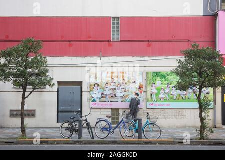 Tokyo, Japan. 18th Dec, 2019. A man stands in front of the Maid Cafe posters a side the street in Akihabara, Tokyo.Akihabara, also called Akiba after a former local shrine, is a district in central Tokyo that is famous for its many electronics shops. In more recent years, Akihabara has gained recognition as the center of Japan's otaku (diehard fan) culture, and many shops and establishments devoted to anime and manga are now dispersed among the electronic stores in the district. Credit: Stanislav Kogiku/SOPA Images/ZUMA Wire/Alamy Live News - Stock Photo