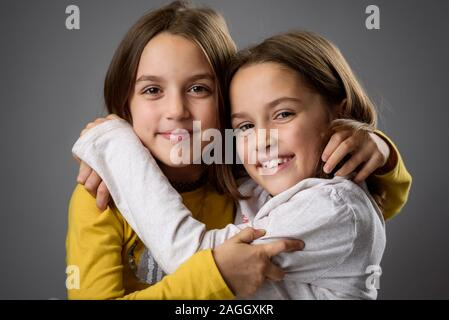 Identical twin girls sisters are posing for the camera. Happy twin sisters looking at the camera, laughing, smiling, hugging, holding hands. Professio - Stock Photo