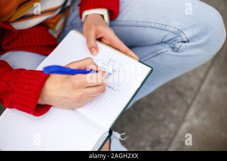 beautiful girl sitting on the street with a notebook and pen in hand, making notes and rests. - Stock Photo