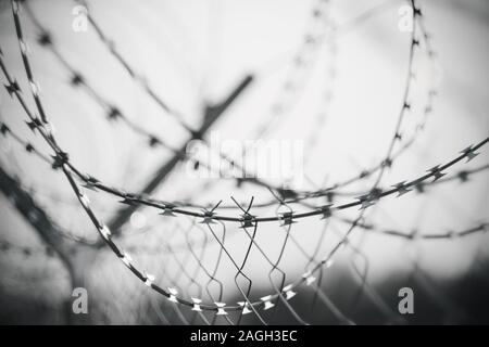 Black-and-white grim sad image of barbed wire wrapped on top of a fence enclosing a prison or restricted area. - Stock Photo