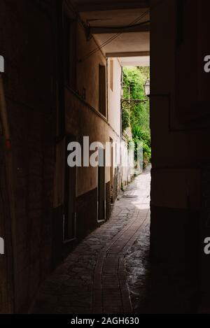 The dark arch in the Italian house. Typical Italian narrow street.