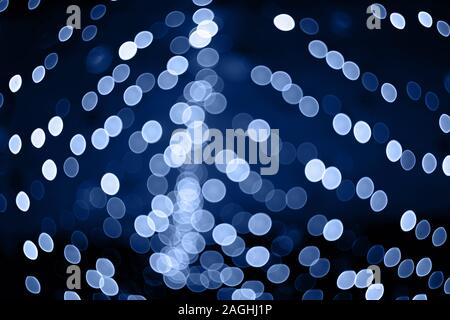 Trendy color of the year 2020. Photo of blue bokeh lights on black background. Perfect for overlay. - Stock Photo