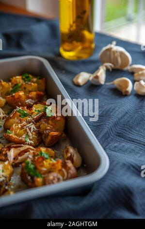 Freshly baked potatoes in a oven tray with fresh garlic and olive oil - Stock Photo