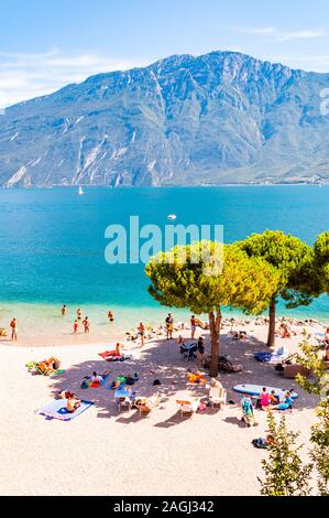 Limone Sul Garda, Lombardy, Italy - September 12, 2019: Cozy beach on western coast of the lake. People swimming sunbathing on the shore under high ev - Stock Photo