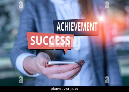 Text sign showing Achievement Success. Business photo showcasing status of having achieved and accomplished an aim Woman in grey suites holds mobile p