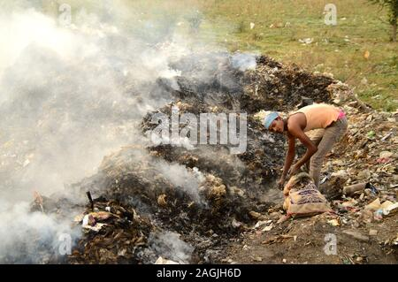 AMRAVATI, MAHARASHTRA, INDIA - APRIL 09, 2014: Unidentified rag pickers search for recyclable material in the garbage. Land and air pollution in India Stock Photo